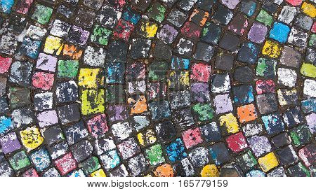 Many colored painted cobble stone pavement in after rain