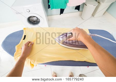 POV Perspective View Woman Hand Ironing Clothes On Ironing Board At Home