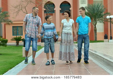 big family in front of hotel, mother, father and sons