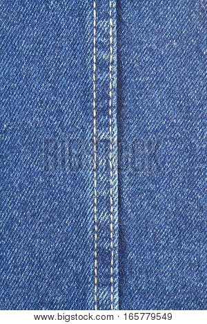 Texture of blue jeans fabric with yellow double stitching in center