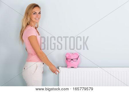 Smiling Young Woman Adjusting Thermostat To Reduce Heating To Save Money On Energy Bill