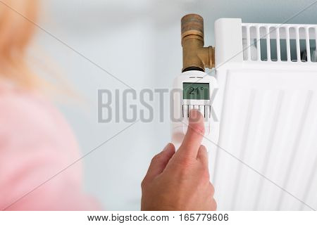 High Angle View Of Person's Hand Adjusting Temperature On Thermostat To Save Money