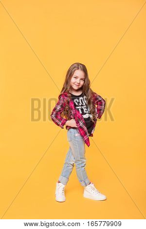 Full length portrait of happy little girl in casual hipster clothes on the yellow background