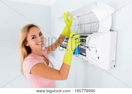 Portrait Of Smiling Woman Cleaning The Air Conditioner With Spray Bottle