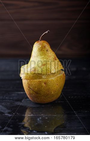 Single cutted pear on wooden rustic background with reflection Minimal style. Vertical shot