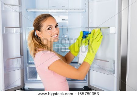 Young Happy Cleaning Lady Cleaning The Empty Refrigerator Door With Spray Bottle And Sponge