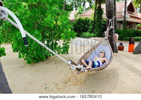Boy Enjoying A Hammoc On Beautiful Tropical Beach