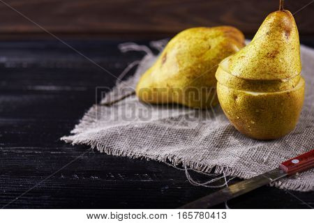 cutted pears and knife on wooden rustic background.