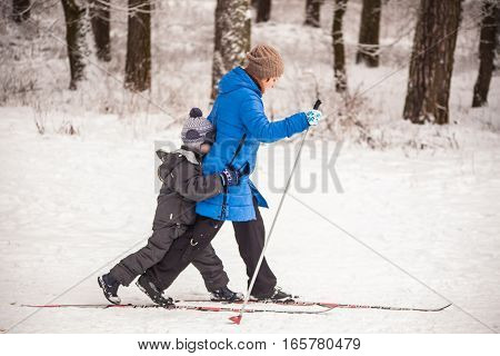 GRODNO BELARUS - JANUARY 15 2017. Mom teach son to ski in the winter forest.