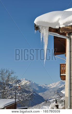 stalactite on a snowy roof under blue sky
