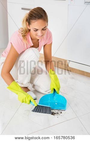 Smiling Woman Sweeping Floor With Broom And Dustpan In The Kitchen