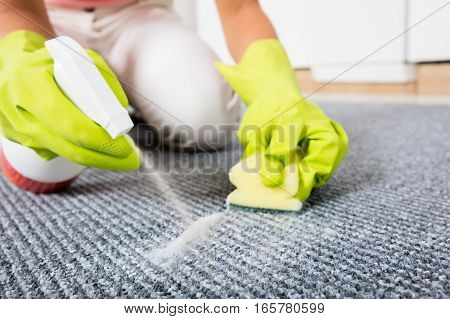 Close-up Of Woman Hand Spraying Detergent On The Carpet Or Rug