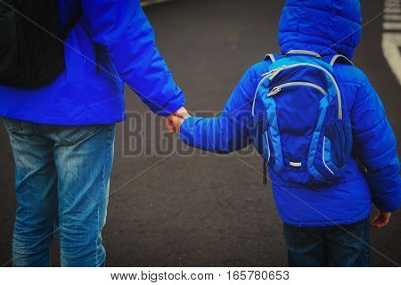 father holding hand of little son with backpack on the road