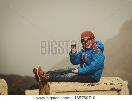 little boy playint with toy plane in mountains, travel concept