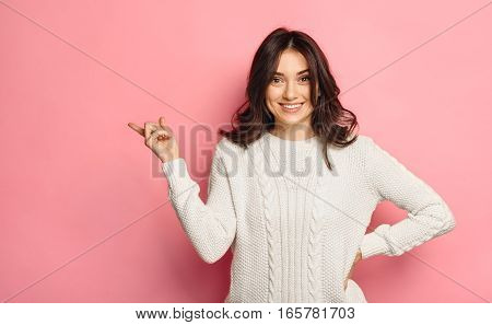 Happy smiling beautiful young woman in white winter sweater showing copyspace over vivid pink color background