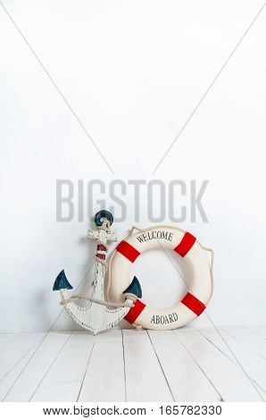 Anchor and life buoy on a white wooden floor.