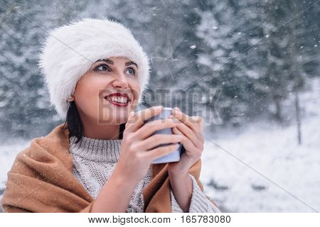 Woman with cup of hot tea on snowy forest background