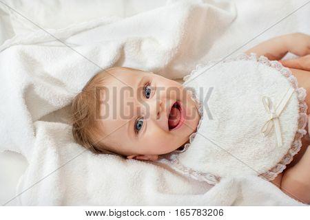 sweet happy little girl lying in bed