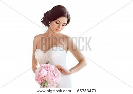 Beautiful bride perfect style. Wedding hairstyle make-up luxury wedding dress and bride's bouquet. Young attractive multi-racial Asian Caucasian model like a bride isolated on white background looking at bouquet.