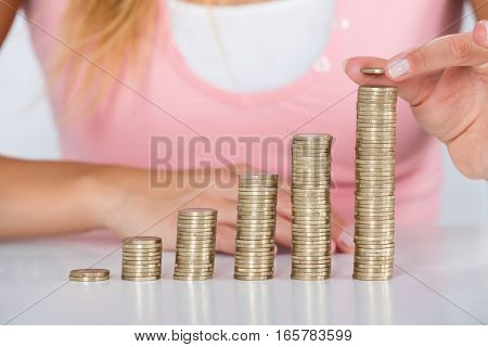 Close-up Of Woman Hand Inserting Coin On The Stack Of Coins At White Desk