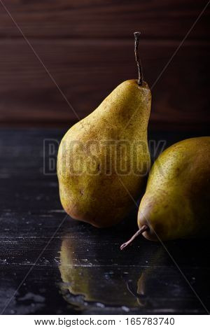 Two pears on wooden rustic background with reflection Minimal style. Vertical shot