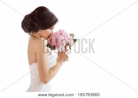Beautiful bride perfect style. Wedding hairstyle make-up luxury wedding dress and bride's bouquet. Young attractive multi-racial Asian Caucasian model like a bride isolated on white background smells bouquet. Side view