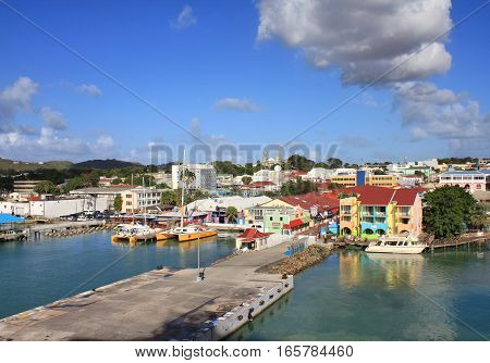 SAINT JOHN'S ANTIGUA - FEBRUARY 19 2014: Waterfront with pier and colorful houses in St John's Antigua and Barbuda. Antigua is a popular destination for cruise ships