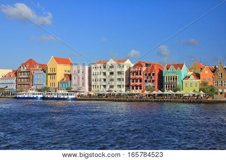 WILLEMSTAD CURACAO - FEBRUARY 11 2014: Waterfront with harbour and colorful houses in Willemstad. The city center is UNESCO World Heritage Site.