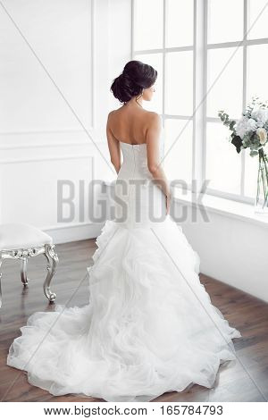 Beautiful bride looking at window. Studio shot in white room from behind. Young gorgeous model in bride's dress in full length