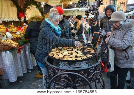 KRAKOW POLAND - DECEMBER 4 2016: Christmas market stall with Grilled cheese oscypek.The annual Christmas markert in the Market Square is a popular tourist attraction