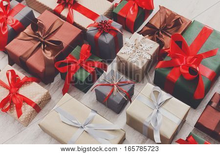 Lots of Gift boxes on wood background. Presents in craft and colored paper decorated with red ribbon bows and snowflakes. Christmas, valentine, birthday holidays concept.