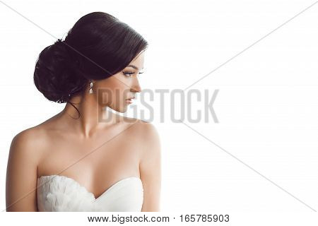 Beauty portrait of bride wearing fashion wedding dress with feathers with luxury delight make-up and hairstyle, studio indoor photo. Young attractive multi-racial Asian Caucasian model. Profile of sensual beautiful young woman like a bride isolated white