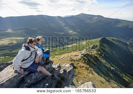 Couple Of People In The Mountains Sit On The Rocks