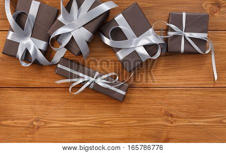 Presents for any holiday concept. Gift boxes frame, top view with copy space on wood table background. Border of packages with satin ribbons for christmas, valentine day or birthday