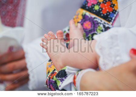 Newborn baby feet. Baby christening. Ceremony in a Christian Church.