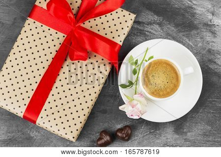 Espresso coffee in a white cup a pink rose a gift with a red tape and chocolates on a dark background. Top view. Food background.