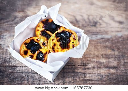 Pasteis de Nata - creamy egg tart with sweet curstard black crust and sugar powder on wooden background. Pasteis de Belem pastry