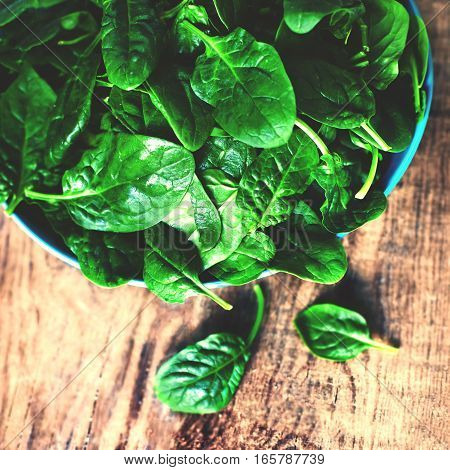 Spinach leaves in a bowl on rustic wooden table close up with copyspace.