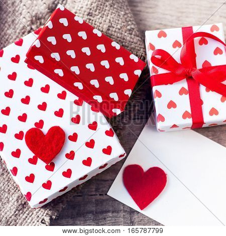 Valentines day Gift box with red bow ribbon paper and hearts on wooden background