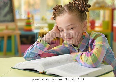 little girl doing homework in her room