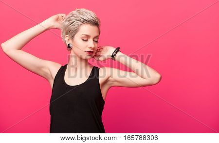 Blonde with fashionable Hairstyle on pink background. Young woman with stylish haircut and bright makeup posing over vivid color wall with copy space