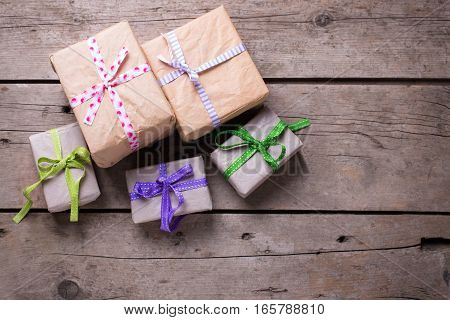 Festive gift boxes with presents on aged wooden background. Selective focus. Place for text. Top view.