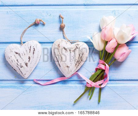 White and pink spring tulips and two decorative hearts on blue background. Pastel colors. Shubby chic. Selective focus.