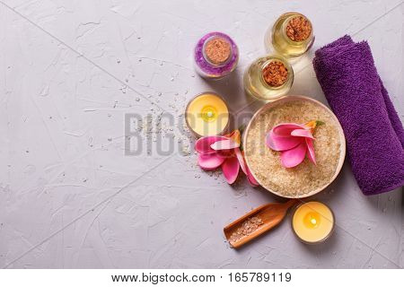 Spa or wellness setting in yellow and violet colors. Bottles with aroma oil sea salt in bowl towel and flowers on grey textured background. Selective focus. Place for text.