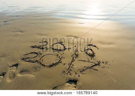 New Year 2017 Written On Seashore Sand At Sunrise.
