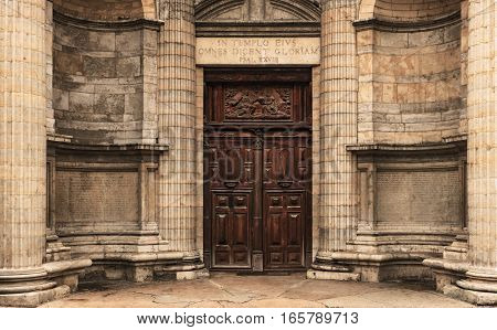 This rectangle wooden double door is the entrance of the St. Nizier christian church in Lyon. The round wall is decorated by columns and Latin inscriptions. In the stone arch stands a quote from Psalm 28