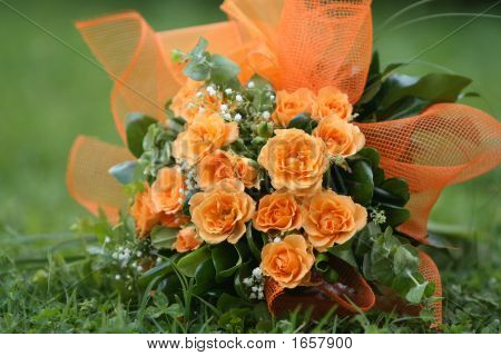 Bouquet Of Orange Roses Laying On The Grass