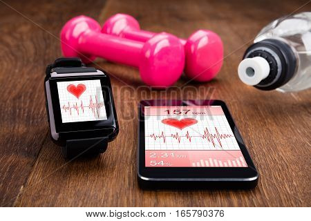 Mobile Phone With Smart Watch Showing Health Monitoring App And Gym Equipment On Wooden Floor