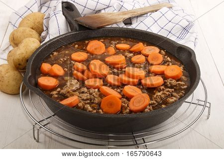 fried minced meat with sauce and fresh carrots in a pan