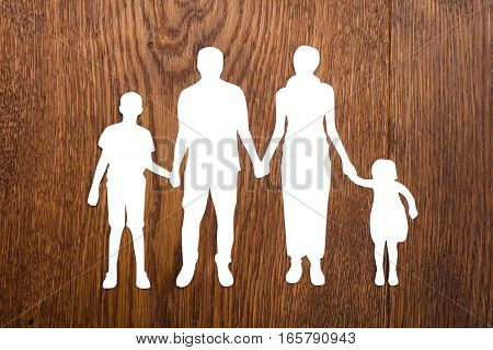 High Angle View Of Family Papercut On Wooden Desk